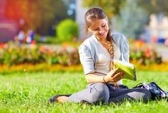 Muchacha linda con el cuaderno que se sienta en parque colorido Imagen de archivo