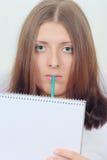 Muchacha linda con el cuaderno y el lápiz Foto de archivo