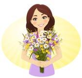 Muchacha linda con el manojo de flores salvajes Foto de archivo libre de regalías