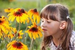 Muchacha linda con el olor del placer las flores fotografía de archivo