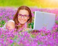 Muchacha linda con el ordenador portátil al aire libre Imagen de archivo libre de regalías