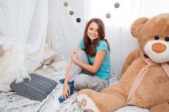Muchacha linda con el oso grande de la felpa que se sienta en sitio de niños Imagen de archivo