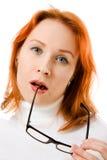 Muchacha linda con el pensamiento de los vidrios del pelo que desgasta rojo Fotografía de archivo