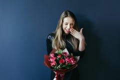 Muchacha linda con el ramo de tulipanes rojos Fotografía de archivo