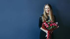 Muchacha linda con el ramo de tulipanes rojos Imagen de archivo libre de regalías