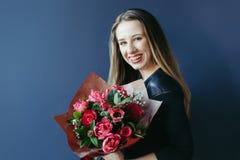 Muchacha linda con el ramo de tulipanes rojos Foto de archivo