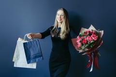 Muchacha linda con el ramo de tulipanes y de paquetes rojos Imagen de archivo libre de regalías