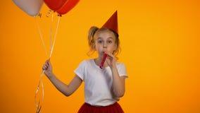Muchacha linda con el ventilador del partido que sostiene los balones de aire y que celebra el cumpleaños, feliz almacen de video