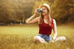 Muchacha linda con la cámara el otoño de la hierba Imagen de archivo