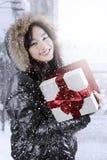 Muchacha linda con la caja de la chaqueta del invierno y de regalo de los controles Fotografía de archivo