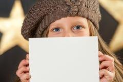 Muchacha linda con la gorrita tejida que oculta detrás de la tarjeta blanca. Foto de archivo