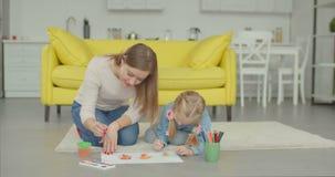 Muchacha linda con la madre que hace la pintura en casa metrajes