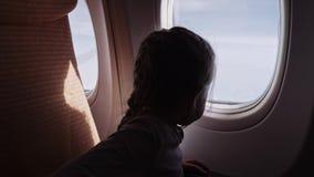 Muchacha linda con la piruleta que mira la ventana en el aeroplano