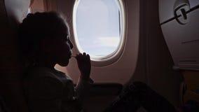 Muchacha linda con la piruleta que se sienta en el aeroplano almacen de video