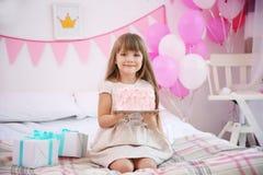 Muchacha linda con la torta que se sienta en cama en el sitio adornado para la fiesta de cumpleaños Fotografía de archivo libre de regalías