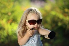 Muchacha linda con las gafas de sol al aire libre Imagenes de archivo