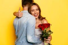 Muchacha linda con las rosas rojas que muestran un pulgar mientras que abraza a su novio foto de archivo libre de regalías