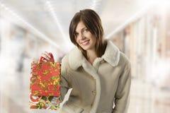 Muchacha linda con los actuales bolsos de compras Foto de archivo