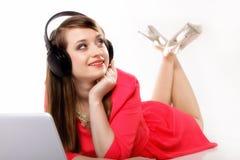 Muchacha linda con los auriculares y la mentira del ordenador portátil Foto de archivo libre de regalías