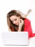 Muchacha linda con los auriculares y la mentira del ordenador portátil Imagenes de archivo