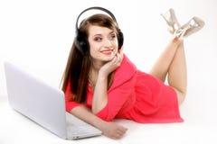 Muchacha linda con los auriculares y la mentira del ordenador portátil Imágenes de archivo libres de regalías