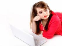 Muchacha linda con los auriculares y la mentira del ordenador portátil Fotografía de archivo libre de regalías