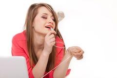 Muchacha linda con los auriculares y la mentira del ordenador portátil aislada Fotos de archivo