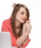 Muchacha linda con los auriculares y la mentira del ordenador portátil aislada Imagen de archivo libre de regalías