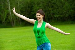 Muchacha linda con los brazos abiertos en campo verde. Fotografía de archivo