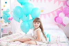 Muchacha linda con los globos que se sientan en cama en el sitio adornado Imagen de archivo libre de regalías