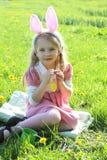 Muchacha linda con los oídos que llevan del conejito en la hierba verde de la primavera Foto de archivo