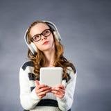 Muchacha linda con los teléfonos principales que sostienen la tableta Fotos de archivo