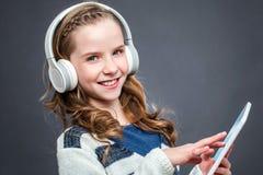 Muchacha linda con los teléfonos y la tableta principales Fotos de archivo libres de regalías