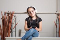 Muchacha linda con los vidrios que escucha la música Foto de archivo libre de regalías