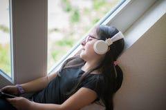 Muchacha linda con los vidrios que escucha la música Fotos de archivo