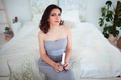 Muchacha linda con maquillaje en un vestido de noche azul que se sienta en la cama En las manos que llevan a cabo una vela foto de archivo libre de regalías