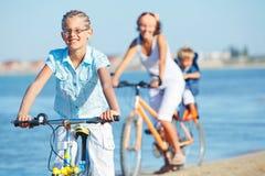 Muchacha linda con sus bicis del paseo de la madre y del hermano Fotografía de archivo libre de regalías