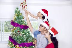 Muchacha linda con sus padres que adornan el árbol de navidad Foto de archivo libre de regalías