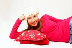 Muchacha linda con un casquillo y una almohada que mienten en el backgr blanco Foto de archivo libre de regalías