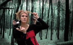 Muchacha linda con un cepillo para el pelo en bosque del otoño del invierno Fotos de archivo