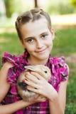 Muchacha linda con un conejo en el jardín. Imagenes de archivo