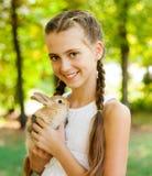 Muchacha linda con un conejo en el jardín. Foto de archivo libre de regalías