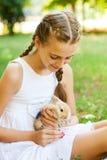 Muchacha linda con un conejo en el jardín. Fotografía de archivo