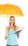 Muchacha linda con un libro bajo el paraguas contra Imagen de archivo libre de regalías