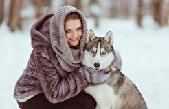 Muchacha linda con un perro fornido en el fondo del bosque del invierno, clos Fotografía de archivo