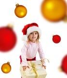 Muchacha linda con un regalo y las esferas de Navidad Fotos de archivo libres de regalías