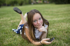 Muchacha linda con un smartphone en las manos de la mentira en hierba verde, mirando la cámara Imagen de archivo libre de regalías