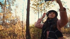 Muchacha linda con un smartphone en naturaleza del otoño almacen de video