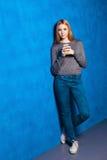 Muchacha linda contra la pared azul Imagenes de archivo