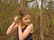 Muchacha linda de 8 años que pone las flores en pelo Imagenes de archivo